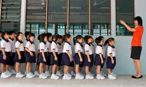 A primary school teacher in Singapore gets her pupils to line up on the first day of the school term
